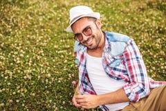 Tillfällig man som väljer en blomma från ett fält och leenden Royaltyfria Bilder