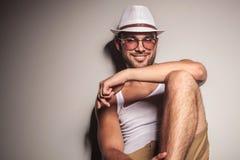 Tillfällig mansammanträde och benägenhet på en vit vägg Fotografering för Bildbyråer
