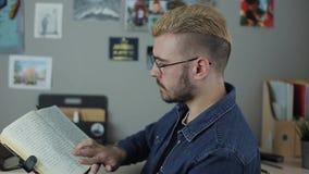 Tillfällig mogen hisptermanstudent med gult hår för stilfull frisyr som sitter det hemmastadda kontoret som läser en stor brun bo arkivfilmer