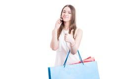 Tillfällig nätt kvinna med shoppingpåsar som kallar på mobiltelefonen Arkivfoton