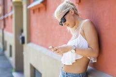 Tillfällig seende blond flicka som använder hennes smartphone Arkivbild