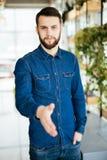 Tillfällig skäggig skaka för hand för håll för skjorta för mankläder som kontrollerad blå hälsar över den vita tegelstenväggen Arkivbild