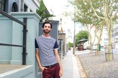 Tillfällig stilig stående yttersida för ung man i randig skjorta Fotografering för Bildbyråer