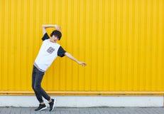 Tillfällig student som dansar till musiken på en gul väggbakgrund Aktivt livsstilbegrepp kopiera avstånd royaltyfri foto