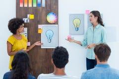 Tillfällig ung affärskvinna som ger presentation till kollegor arkivfoto