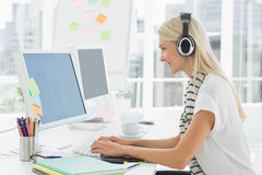 Tillfällig ung kvinna med hörlurar med mikrofon genom att använda datoren i regeringsställning Royaltyfri Foto