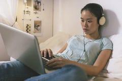 Tillfällig ung kvinna som ligger på säng och hemma använder bärbara datorn Fotografering för Bildbyråer