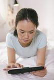 Tillfällig ung kvinna som ligger på säng och hemma använder den digitala minnestavlan Arkivfoto