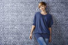 Tillfällig ung kvinna som lutar till väggen arkivbild