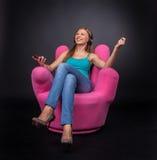 Tillfällig ung kvinna som lyssnar till spelaren mp3 Royaltyfria Bilder