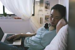 Tillfällig ung kvinna som sover på säng, medan genom att använda bärbara datorn hemma Arkivbild