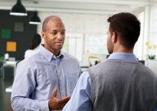 Tillfälliga affärsmän som talar på kontoret Arkivfoto
