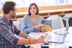 Tillfälliga affärspartners på arbete på konferenstabellen Arkivbild