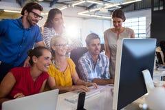 Tillfälliga kollegor som arbetar på en dator royaltyfria bilder