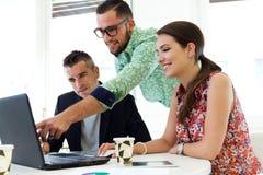Tillfälliga ledare som tillsammans arbetar på ett möte med bärbara datorn Arkivfoto