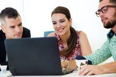 Tillfälliga ledare som tillsammans arbetar på ett möte med bärbara datorn Arkivfoton