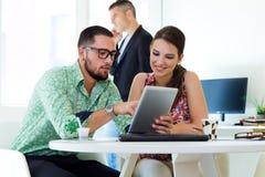 Tillfälliga ledare som tillsammans arbetar på ett möte med den digitala fliken Royaltyfri Bild