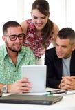 Tillfälliga ledare som tillsammans arbetar på ett möte med den digitala fliken Arkivfoto