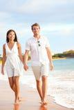 Tillfälliga par som går på strandinnehavhänder Royaltyfri Fotografi