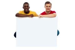 Tillfälliga unga grabbar som poserar med den blanka affischtavlan Royaltyfria Foton