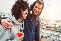 Tillfälliga unga par som ler utomhus- gå i hamnen royaltyfri fotografi