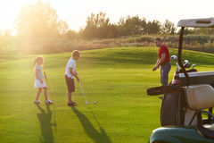 Tillfälliga ungar på en golf sätter in hållande golfklubbar Solnedgång Arkivbilder