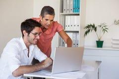 Tillfälligt affärslag som tillsammans arbetar på skrivbordet genom att använda bärbara datorn Royaltyfria Foton