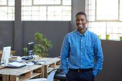 Tillfälligt klätt afrikanskt affärsmananseende i ett modernt kontor arkivfoto