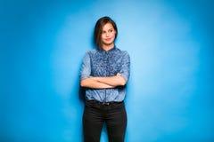 Tillfälligt klätt för ung kvinna på blå bakgrund royaltyfria bilder
