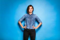 Tillfälligt klätt för ung kvinna på blå bakgrund fotografering för bildbyråer
