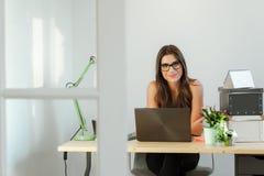 Tillfälligt kvinnasammanträde för affär på skrivbordarbete Arkivbild