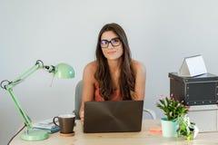 Tillfälligt kvinnasammanträde för affär på skrivbordarbete Royaltyfri Bild