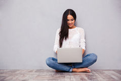 Tillfälligt kvinnasammanträde på golvet med bärbara datorn Royaltyfri Fotografi