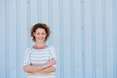 Tillfälligt lyckligt kvinnaanseende vid väggen med korsade armar arkivfoton