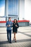 Tillfälligt möte utanför på en solig dag Mellan skilda raser par som går på gatan Arkivfoton