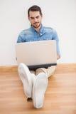 Tillfälligt mansammanträde på golv genom att använda bärbara datorn Arkivfoto