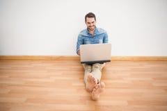 Tillfälligt mansammanträde på golv genom att använda bärbara datorn Arkivbild