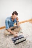 Tillfälligt mansammanträde på golv genom att använda bärbara datorn på telefonen Arkivfoto
