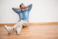 Tillfälligt mansammanträde på golvet som ser upp Royaltyfria Bilder