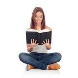 Tillfälligt sammanträde för ung kvinna på golvet som läser en bok Royaltyfri Foto