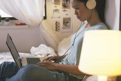 Tillfälligt sammanträde för ung kvinna på säng och användabärbara datorn hemma Arkivfoto