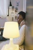 Tillfälligt sammanträde för ung kvinna på säng och användabärbara datorn hemma Arkivfoton