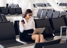 Tillf?llig kvinna som arbetar p? b?rbara datorn i flygplatskorridor Kvinna som v?ntar hans flyg p? flygplatsterminalen som sitter arkivfoton