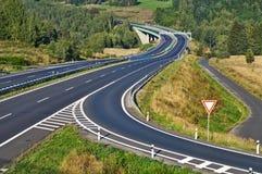 Tillfartsväg till huvudvägen mellan skogar i landskapet Arkivfoton