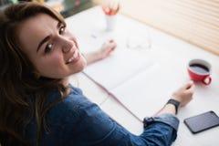 Tillfällig affärskvinna som arbetar på hennes skrivbord Royaltyfri Foto