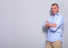 Tillfällig gamal man med armar som korsas på grå färger Arkivfoto