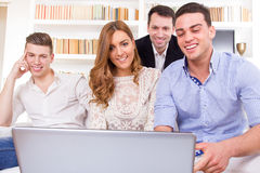 Tillfällig grupp av vänner som sitter på soffan som ser bärbara datorn Arkivbilder