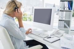 Tillfällig ung kvinna med hörlurar med mikrofon genom att använda datoren Royaltyfri Fotografi