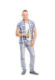 Tillfällig ung man som rymmer en flaska av öl Fotografering för Bildbyråer