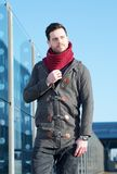Tillfällig ung man som utomhus går i omslag och halsduk Arkivfoto